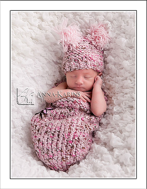 Beautiful newborn baby girl in cocoon, baby bundled up in a wrap, pink newborn baby girl