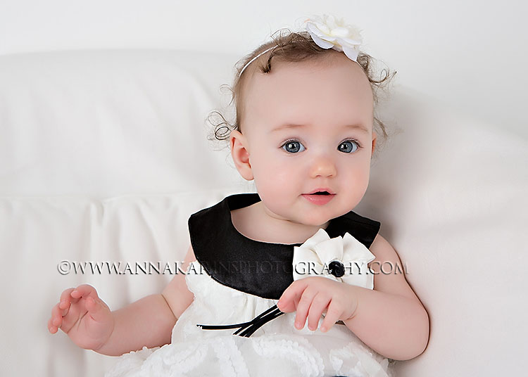 sweet curly haired little sister with blue eyes. Beautiful baby portrait. highkey baby photograph
