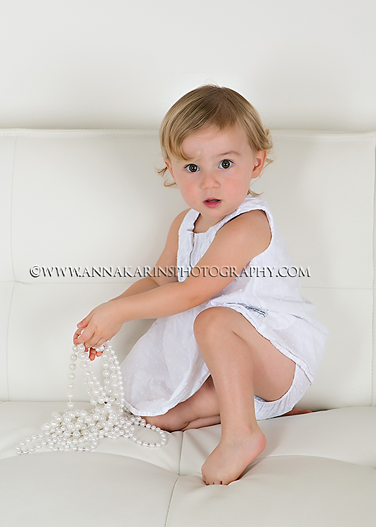 Little girl playing with pearls on white sofa,