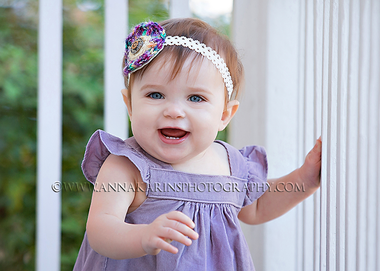 Happy baby girl, sweet little grin from one year old baby girl, traditional southern style portrait with white porch fence