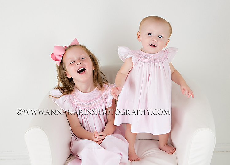 Happy joyous laughing sister moment, sweet little sisters playing
