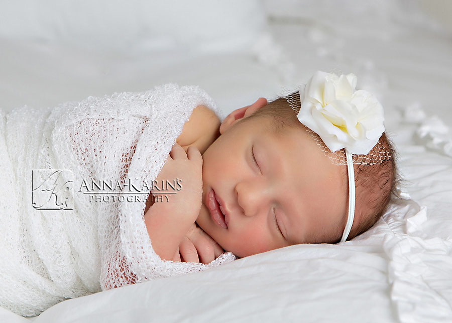 Sweet beautiful newborn baby girl, little baby girl with white flower headband