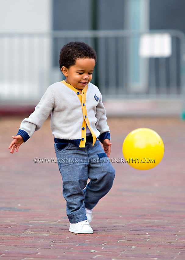 little toddler boy kicking a ball