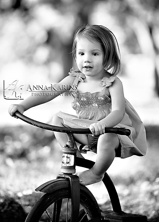 Little girl on tricycle, outside riding trike