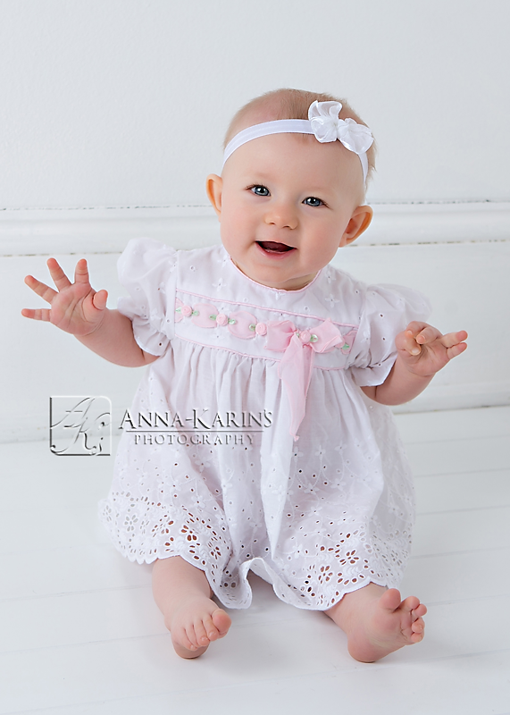 happy baby girl in adorable white dress and hair band