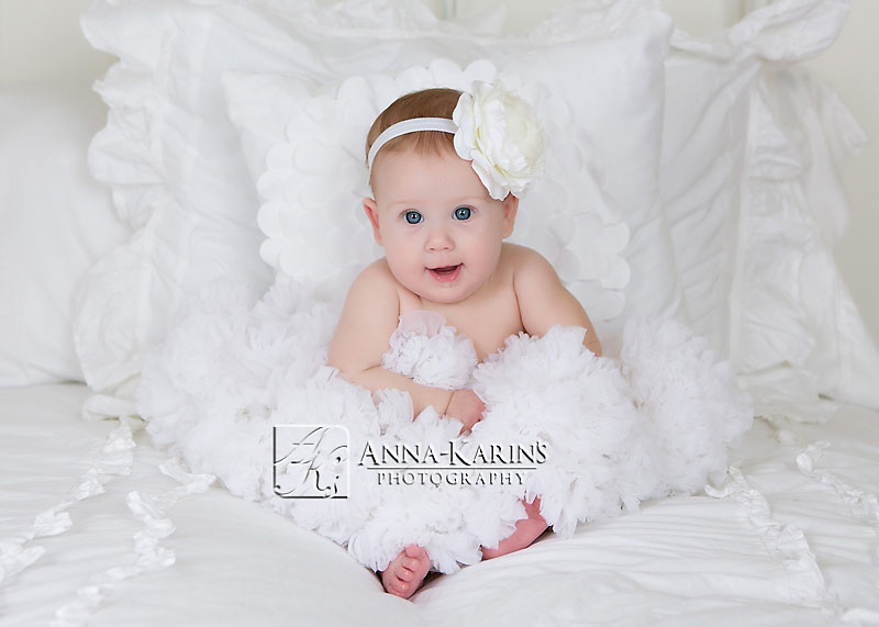 Pretty baby girl sitting on white bedding, adorable blue eyed baby girl