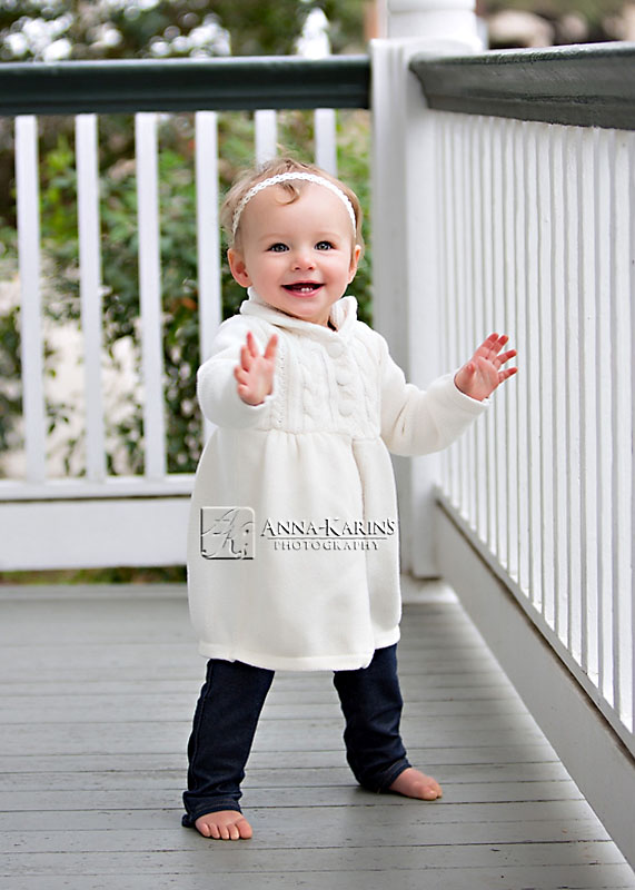 standing up one year old baby girl, outdoor family session with toddler
