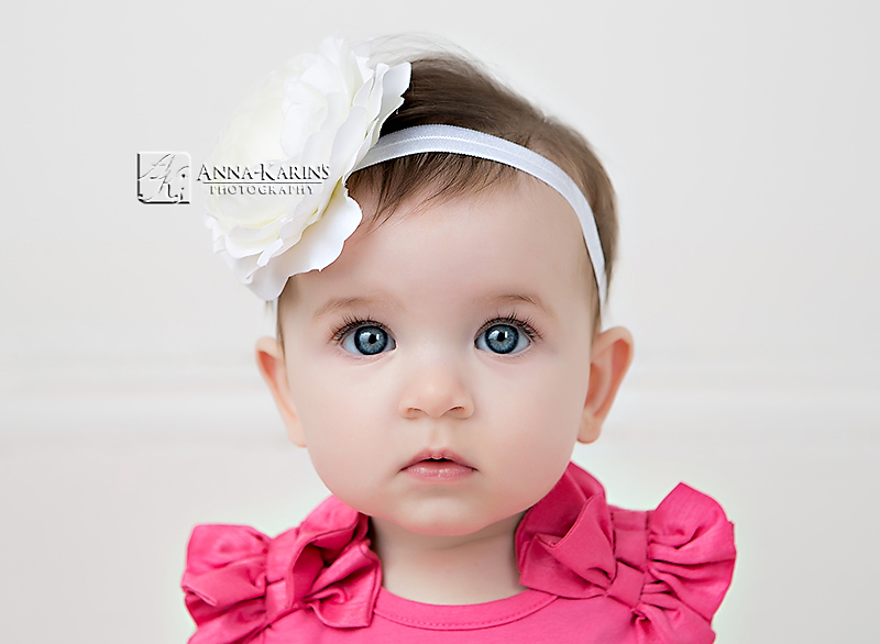 Blue eyed baby girl with white flower head band, gorgeous baby girl