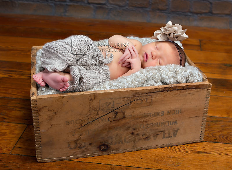 Newborn baby in knitted pants, baby in wooden box on wood floor