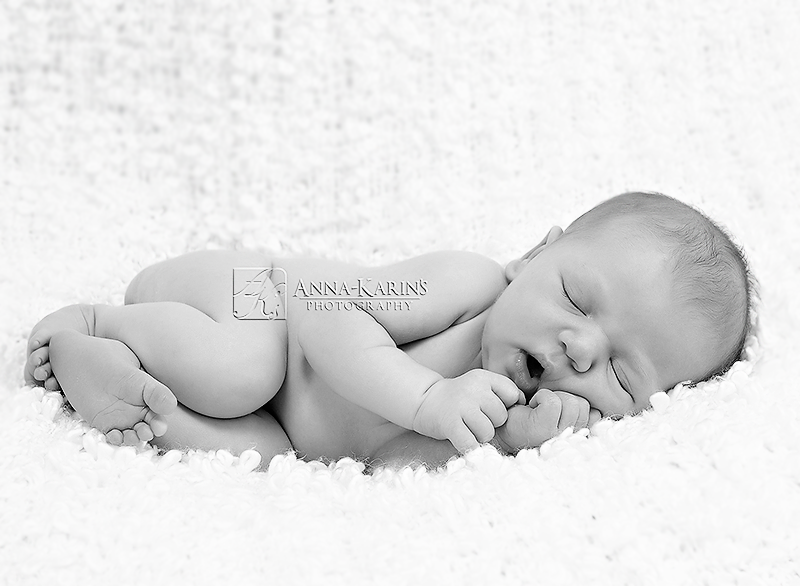 sleepy and curled up newborn baby