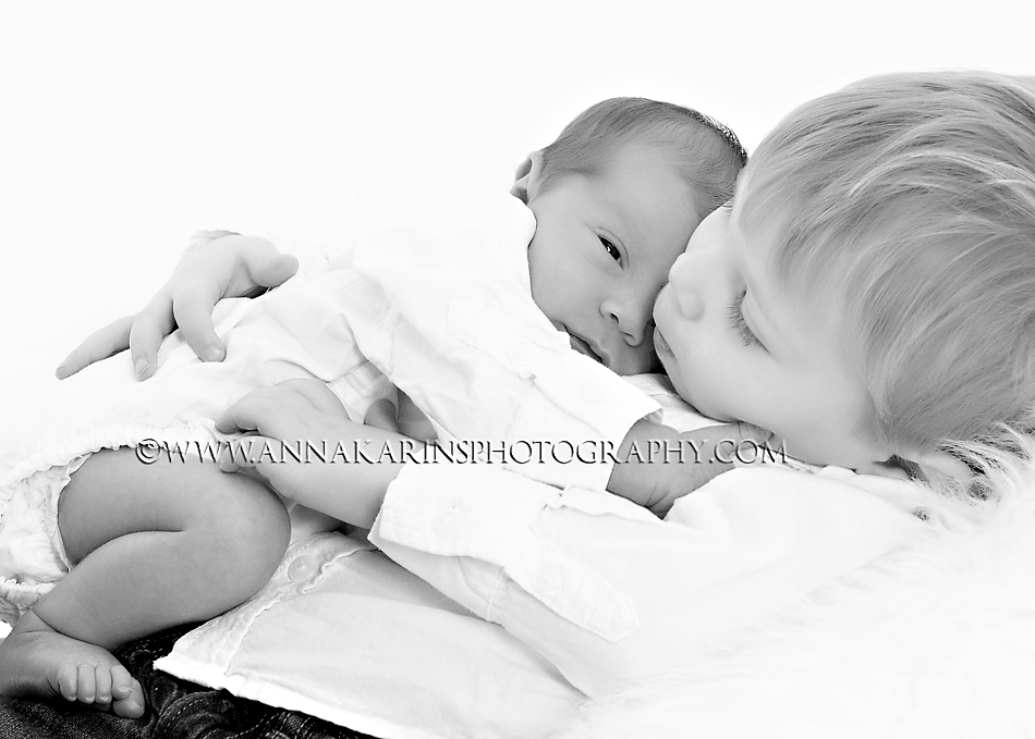 Sweet brothers, big brother holding newborn baby brother