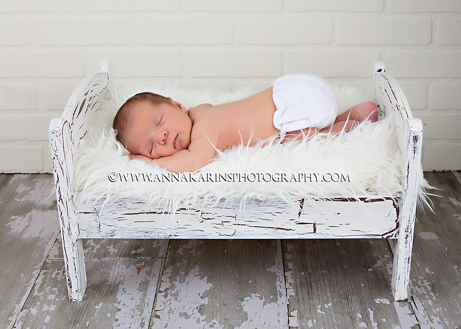 Sleepy newborn in doll bed