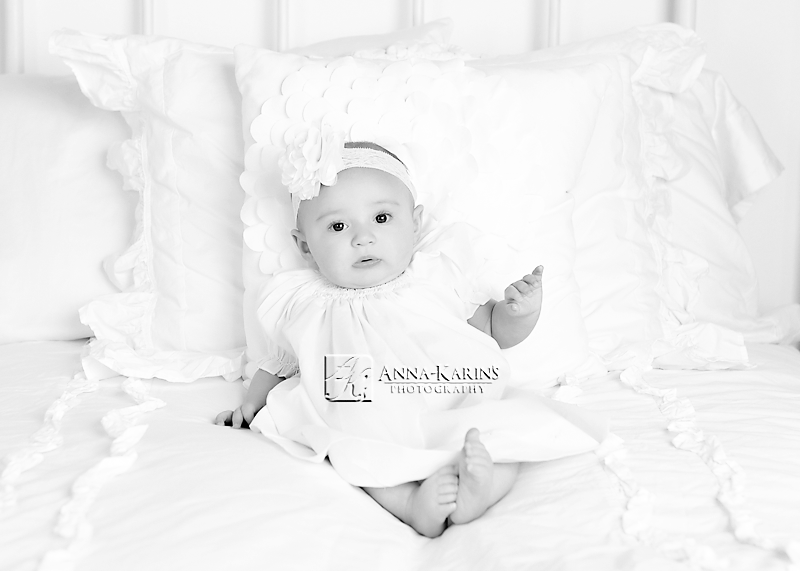 timeless bw portrait of baby girl on white bed