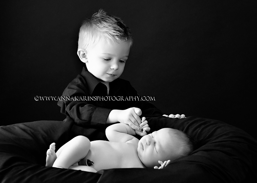 bw portrait of big brother with newborn baby brother