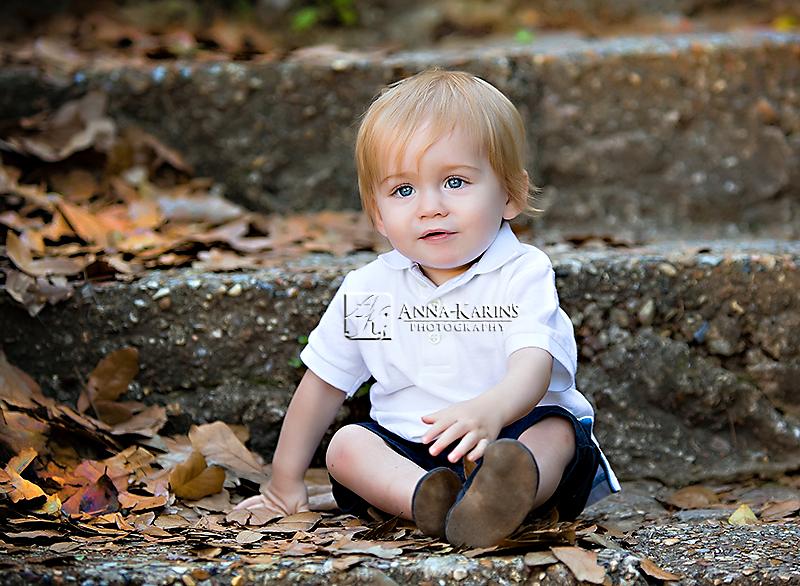 Little boy sitting in leafs outdoors