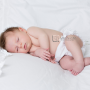 sleepy newborn baby on white