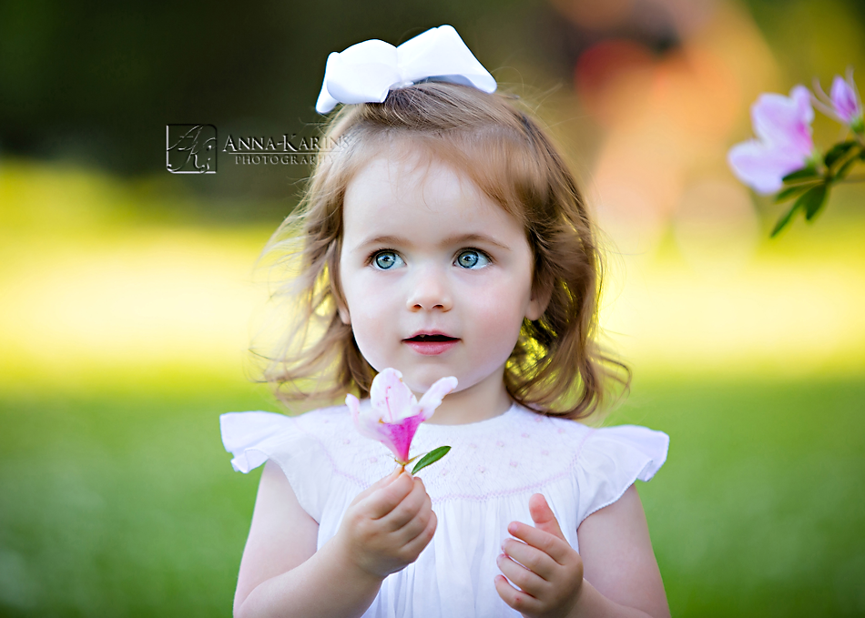 Little sweet girl picking a flower