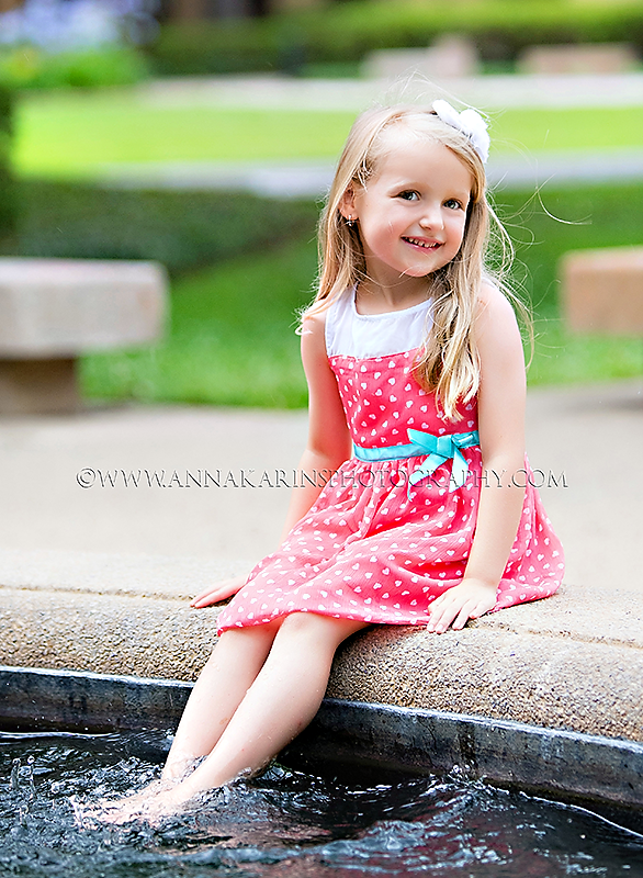 Sweet girl with feet in a fountain