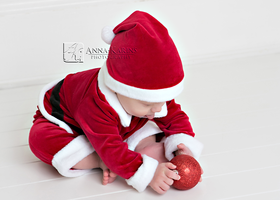 santa baby playing with ornament