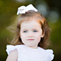 beautiful little girl with smocked dress and bow in hair