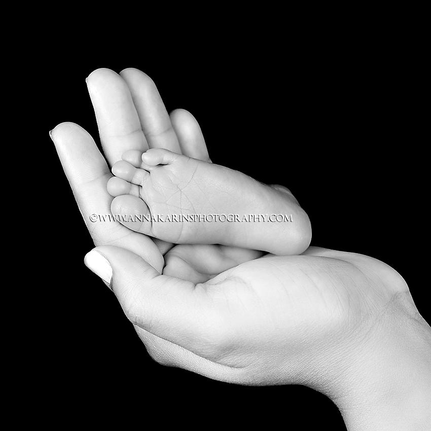 Newborn baby foot in mamas hand