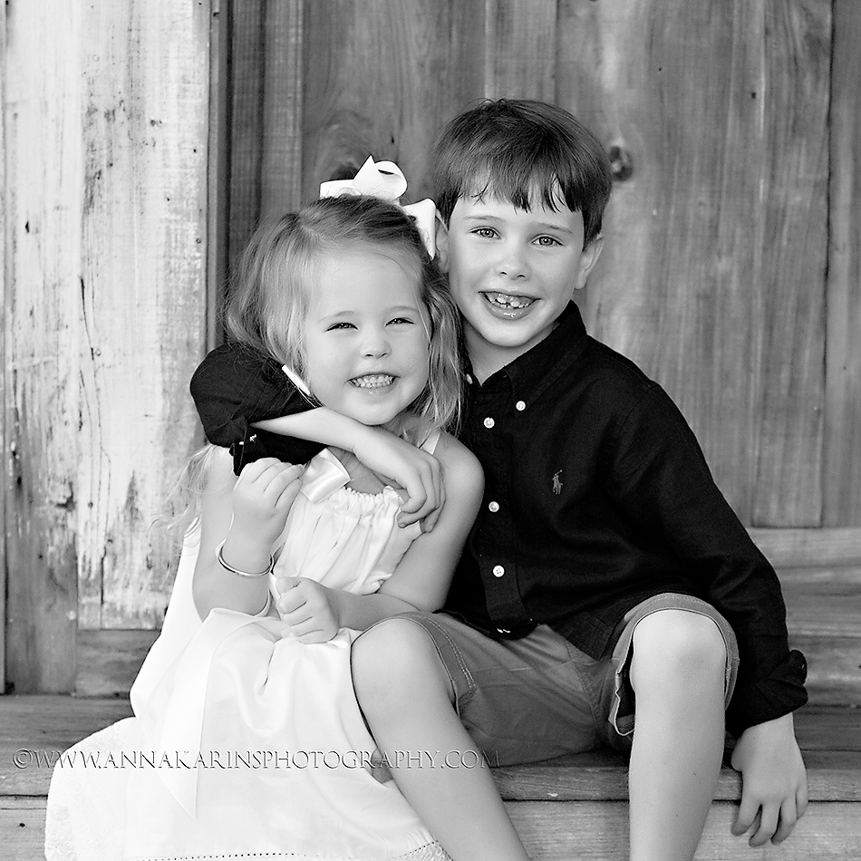 sweet siblings hugging while sitting on a staircase