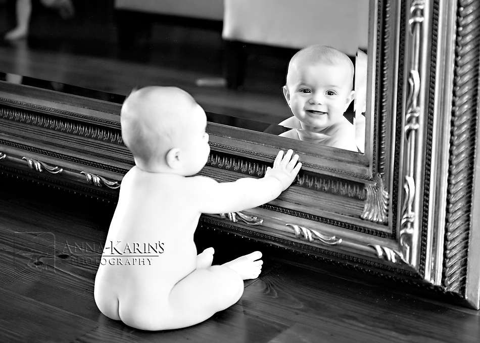 baby seeing his reflection in a mirror