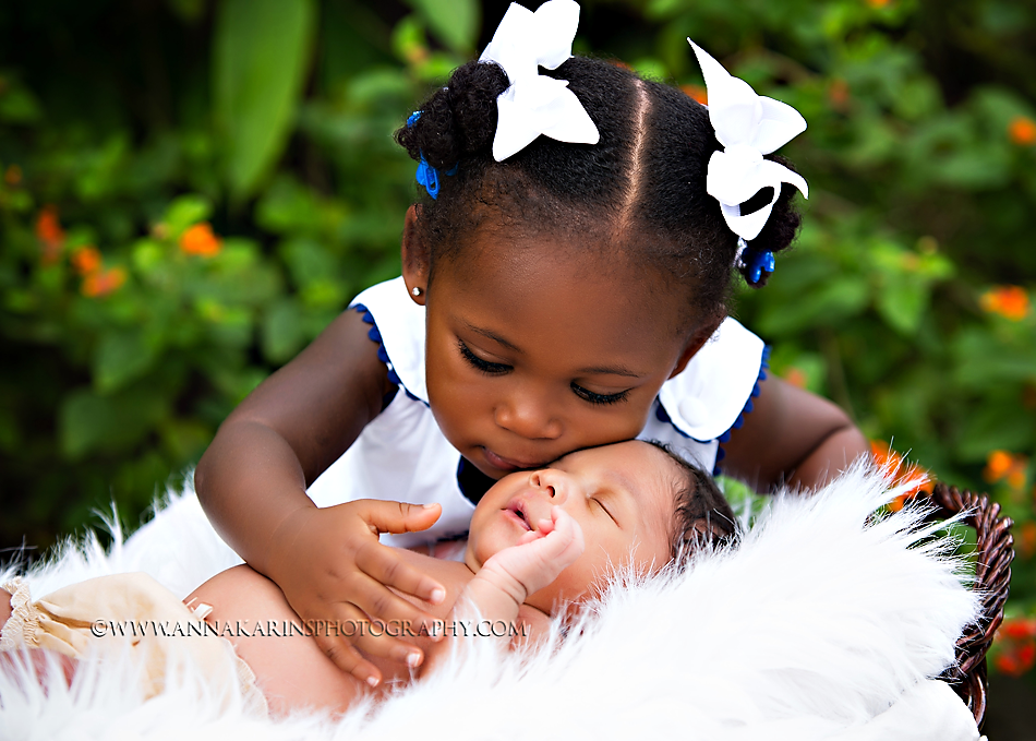 Big sister kissing her newborn sister