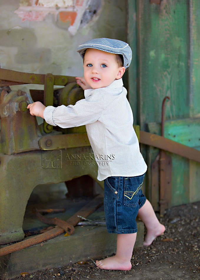 little boy barefoot and in blue jeans playing with tools